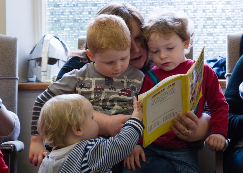 Mums and small children reading a book
